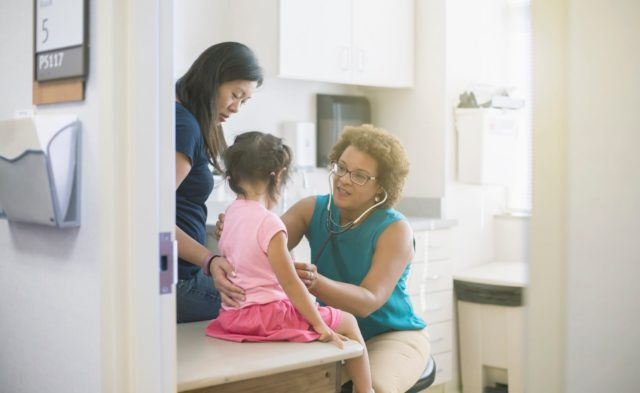 A doctor speaks to a young girl and her mother.