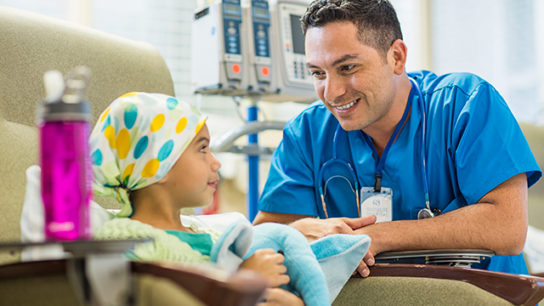A doctor comforts a young patient before chemotherapy.