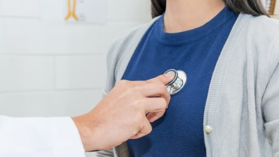 A doctor uses a stethoscope to listen to a patient's heart.