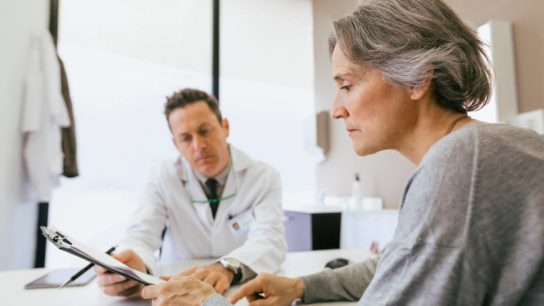A doctor speaks with an elderly patient.