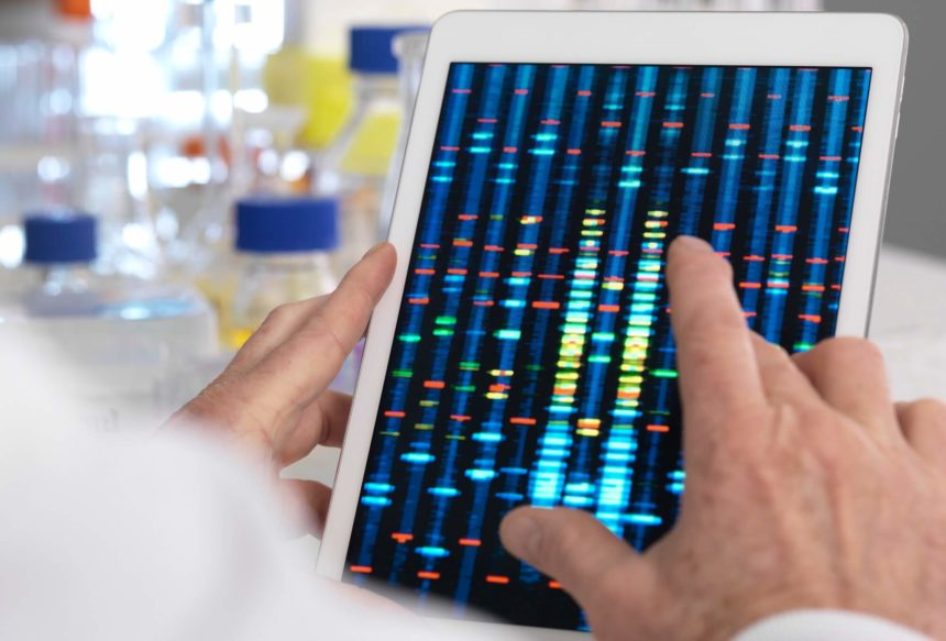 A clinician observes the results of a genetic test on their tablet.