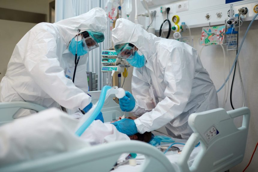 Healthcare workers intubating a COVID patient