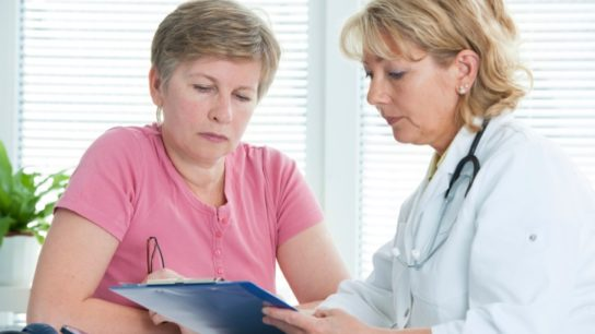 Female doctor and patient reviewing medical record