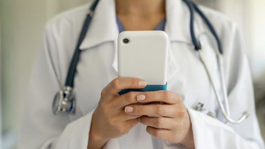 Hands of female doctor holding phone