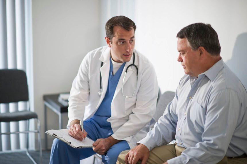 A doctor speaks to an elderly patient.