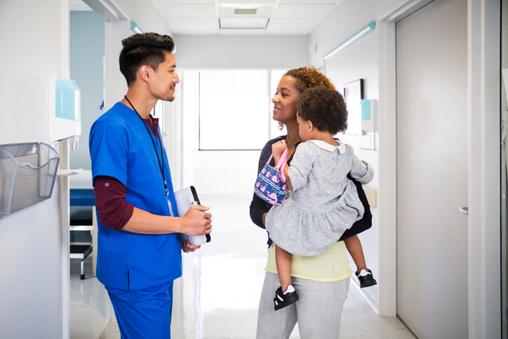 Mother and child talking to doctor.