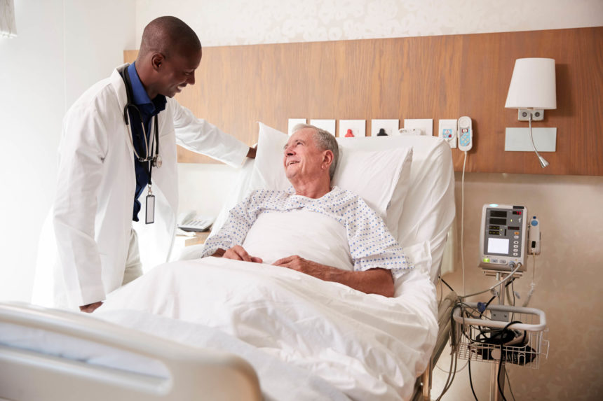 Doctor talking to patient in hospital bed.